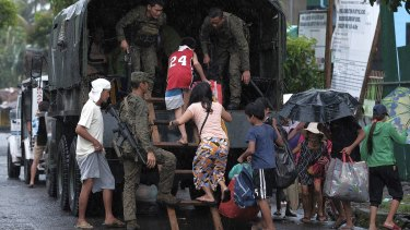 Residents in south-east Manila evacuate in a military truck before the typhoon hits.