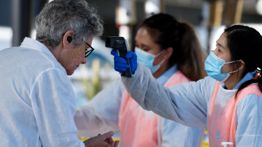 A woman has her temperature checked at the Sydney fish market as the nation deals with the COVID-19 crisis.