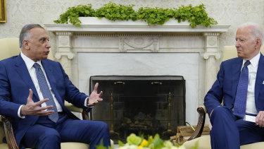 US President Joe Biden, right, listens as Iraqi Prime Minister Mustafa al-Kadhimi speaks during their meeting in the Oval Office.