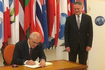Prime Minister signs the guest book at the OECD, overseen by new Secretary-General Mathias Cormann.
