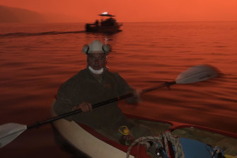 Justin Brady, whose home was destroyed in the fire, seeks refuge on the water in his canoe at Mallacoota.