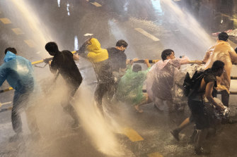 Protesters are hit with water canons as police try to clear an area in Bangkok on Friday.