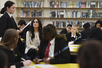 Meghan listens to a student reciting a poem to pupils at the Robert Clack Upper School.