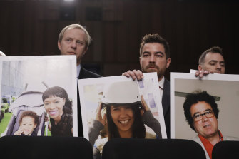 Family members of crash victims holding up photographs of their loved ones at a US Senate hearing last year.