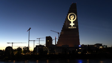 The women's strike logo is projected on the Roche Tower ahead of a nationwide women's strike.