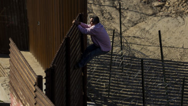 A migrant climbs the border fence to get from Tijuana, Mexico to San Diego in the US.