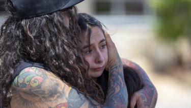 A couple embrace at the makeshift memorial for victims of the mass shooting at a shopping complex in El Paso, Texas.