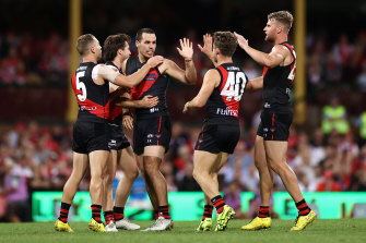 SYDNEY, AUSTRALIA - APRIL 08: Alec Waterman of the Bombers celebrates kicking a goal with team mates during the round four AFL match between the Sydney Swans and the Essendon Bombers at Sydney Cricket Ground on April 08, 2021 in Sydney, Australia. (Photo by Cameron Spencer/Getty Images)