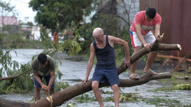 Men cut down a tree that fell due to strong winds as Typhoon Kammuri slammed Legazpi city, Albay province, southeast of Manila, Philippines, earlir this month.