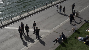 French police work to control people along the Seine river banks in Paris on Wednesday.