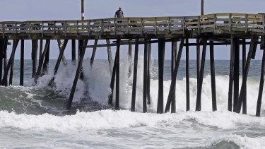 Waves crash under a pier in Kill Devil Hills, NC.