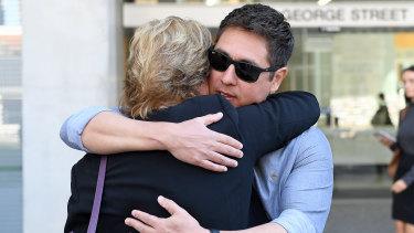 The brother of Fabiana Palhares, Raphael Palhares (right), is consoled after leaving the Supreme Court in Brisbane.
