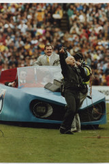 Angry Anderson performs with the Batmobile at the 1991 grand final.