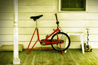 An exercise bike sits abandoned on a country porch.