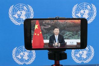 Chinese President Xi Jinping is seen on a phone screen remotely addressing the 75th session of the United Nations General Assembly.