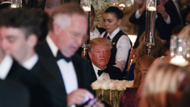 US President Donald Trump sits at his table during a New Year's Eve gala at his Mar-a-Lago resort Sunday.