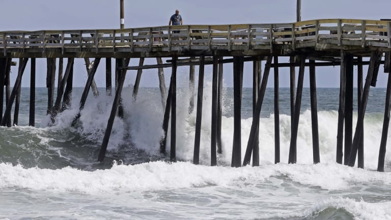 Waves crash under a pier in Kill Devil Hills, NC.