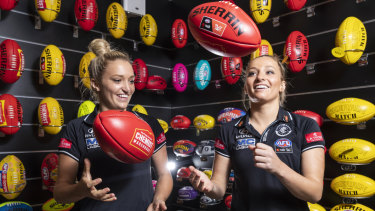Jess (left) and Sarah Hosking, pictured at the Sherrin factory, will be the first twins to play together in an AFLW grand final.