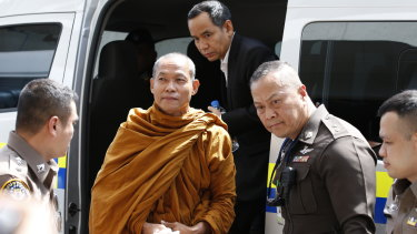 Thai Buddhist monk Phra Buddha Isara is escorted by Thai police officers at the Criminal Court in Bangkok.
