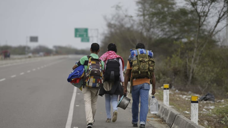 Venezuelan Omar Mujica, right, walks to Lima along the shoulder of the Pan-American Highway with other Venezuelan migrants.