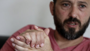 Al Noor mosque shooting survivor Temel Atacocugu gestures during an interview at his home in Christchurch, New Zealand.