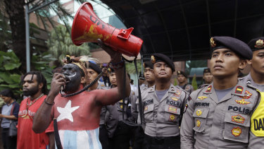 In this March 20, 2017, file photo, a Papuan activist whose body is painted in the colours of 'Morning Star' separatist flag shouts slogans as police officers stand guard during a protest in Jakarta, Indonesia.