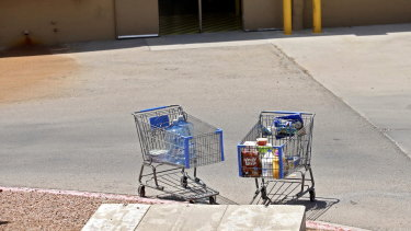 Shopping carts sit next to a curb after a shooting at a Walmart in El Paso, Texas.