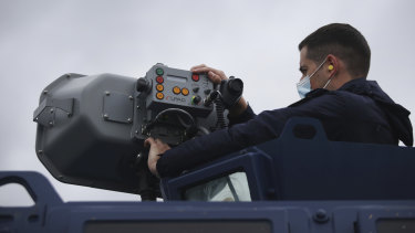 A police officer operates a long range acoustic device, attached to a police vehicle, during a patrol alongside the Greek-Turkish border near the town of Feres, Greece.