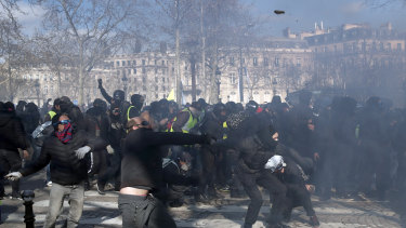 Protesters clash with riot police during a yellow vests demonstration in Paris.