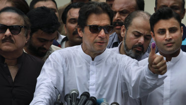 Imran Khan shows his marked thumb after casting his vote.