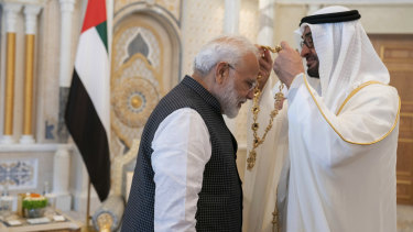Indian Prime Minister Narendra Modi, left, receives a medal during his induction to the Order of Zayed from Sheikh Mohammed bin Zayed Al Nahyan, right, in Abu Dhabi, UAE.