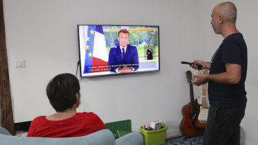 A couple watches Macron's televised address to the nation.