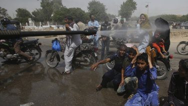 Pakistani volunteer spray water on people to keep them cool as temperatures reached 44 degrees in Karachi on Monday.