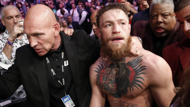 The Irishman is led away by security after the post-fight drama.