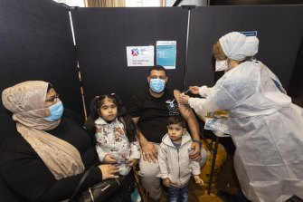 Osama Jabry receiving his COVID-19 vaccination from nurse Sonya El-Abbas, accompanied by his wife Manal Kareen, and children Rokaya and Hussien at Broadmeadows Town Hall vaccination hub.