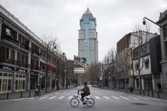 A man bicycles past an empty street on February 8, 2020 in Wuhan, Hubei province, China.