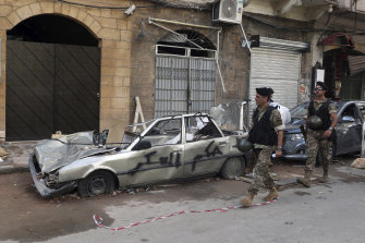"""Soldiers walk past a car with graffiti in Arabic """"Down with the military rule"""", near the site of the recent explosion in Beirut."""