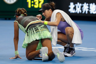 Ajla Tomljanovic assists injured rival Qiang Wang on court.