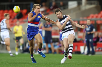Patrick Dangerfield gets a kick away for the Cats as Bailey Smith moves in for the Bulldogs.