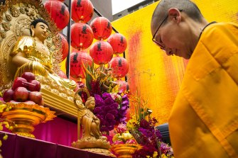 A monk prays at a Buddhist shrine erected in a square in Melbourne's Chinatown.