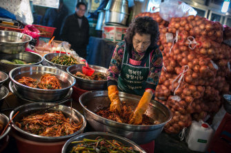 A merchant makes kimchi at a market in Seoul, South Korea. Kimchi is a traditional Korean dish of pickled vegetables served as a main or side dish.