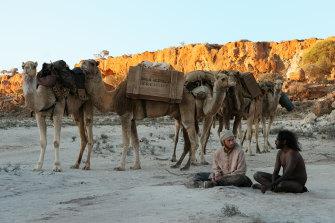 Hanif (Ahmed Malek), Woorak (Baykali Gnambarr) and camel train in a scene from Roderick MacKay's The Furnace.