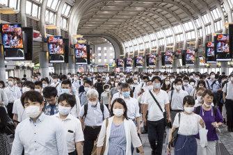 Commuters wearing face masks pass through Shinagawa train station in Tokyo.
