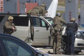 Royal Canadian Mounted Police officers prepare to take a suspect into custody at a gas station in Enfield, Nova Scotia, on Sunday.
