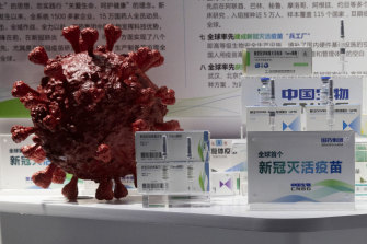 Samples of a COVID-19 vaccine produced by Sinopharm are displayed near a 3D model of the virus.