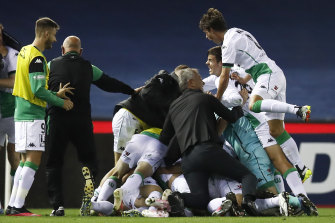 Coach Mark Rudan joins the celebratory pile-on after Western United's last-gasp win over Melbourne Victory.