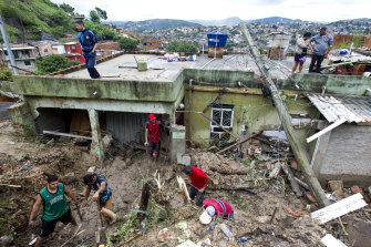 Locals work to clean up mud and debris around houses destroyed by a landslide after heavy rains in the Vila Ideal neighbourhood in Brazil.