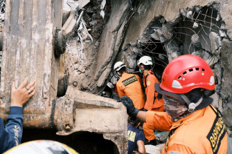 Rescuers search for victims at the ruin of a building damaged by an earthquake in Mamuju, West Sulawesi, Indonesia.
