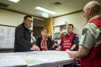Premier Daniel Andrews is briefed by emergency services personnel in Orbost