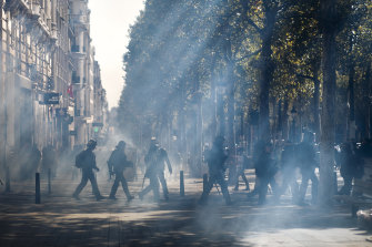 French riot police walk through a tear gas cloud on the Champs Elysees during the Yellow Vest demonstration on Saturday.